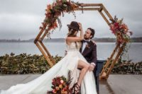 05 a bright fall hexagon wedding arch with dried leaves in burgundy and rust, greenery and blooms
