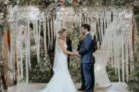 05 a chic macrame wedding backdrop with long fringe, lush greenery and pink blooms on top for a summer wedding