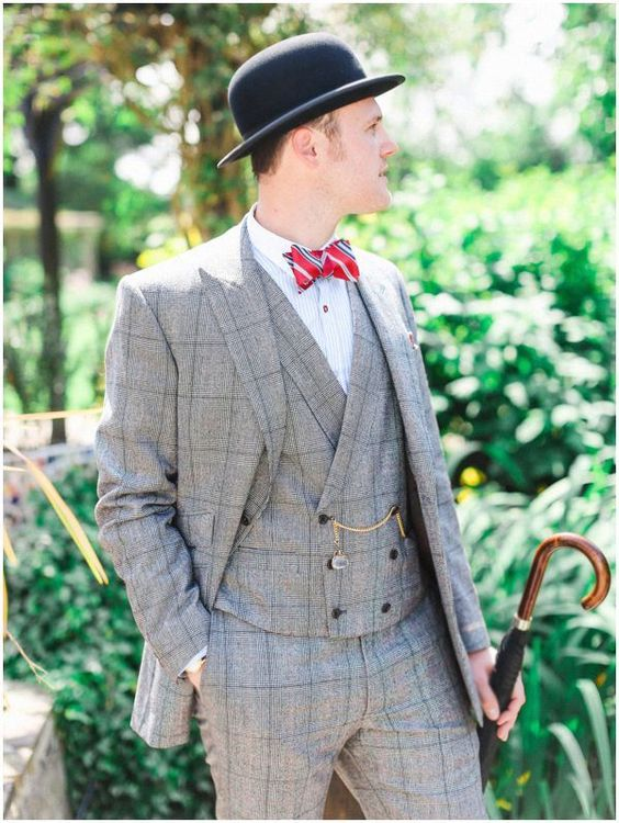 a light grey windowpane three-piece suit, a white shirt, a red striped tie and a black hat plus a chain