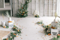 06 The ceremony space was done with greenery, citrus slices, marigold and white blooms, palm leaves