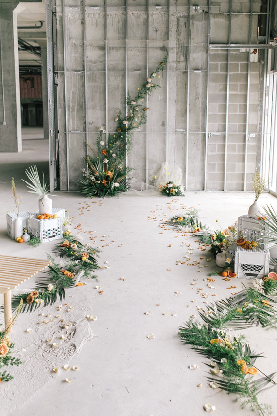 The ceremony space was done with greenery, citrus slices, marigold and white blooms, palm leaves
