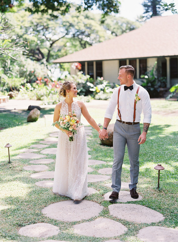 The groom was wearing grey pants, a white shirt, amber suspenders, a black bow tie and brown shoes