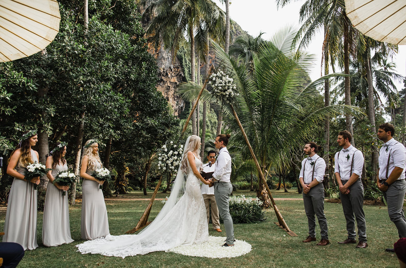 The second ceremony space was done with a triangle arch decorated with white florals and greenery and macrame rugs