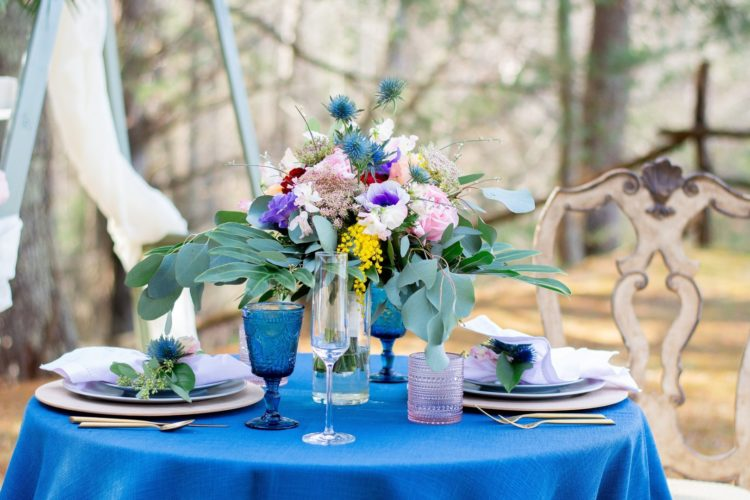 The wedding table setting was done with a bright blue tablecloth and glasses, a colorful floral centerpiece, lavender napkins and pink glasses