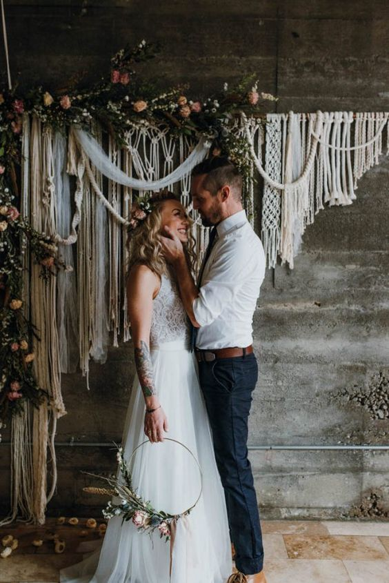 a gorgeous macrame wedding backdrop with greenery and fresh blooms on top feels very free spirited