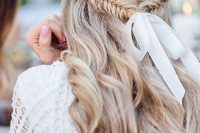06 a wavy half updo with a fishtail braid secured with a white ribbon and a bow is a very relaxed boho idea