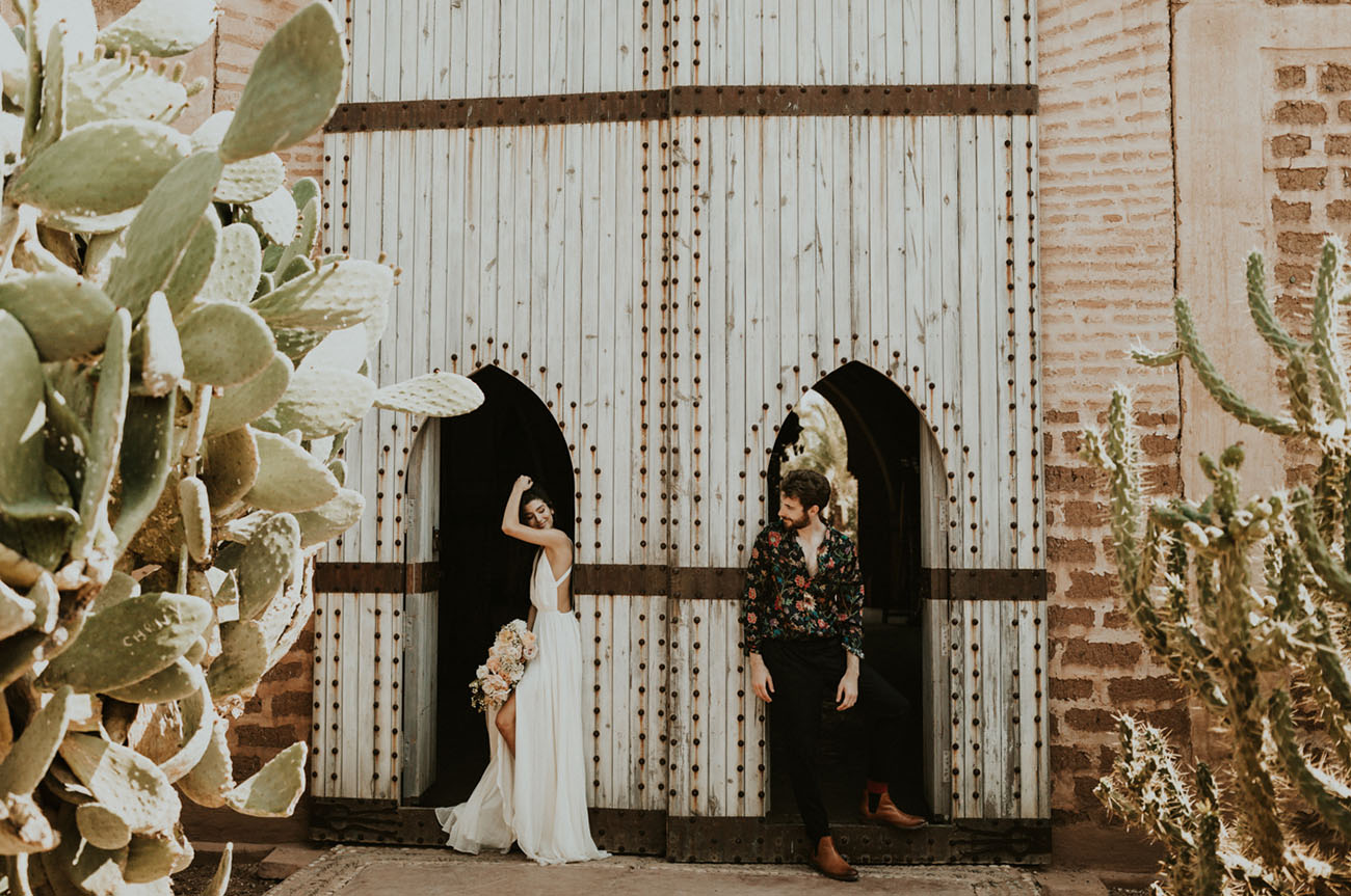 The groom was rocking a chic look with a moody floral shirt, black pants and brown booties for the 70s feel