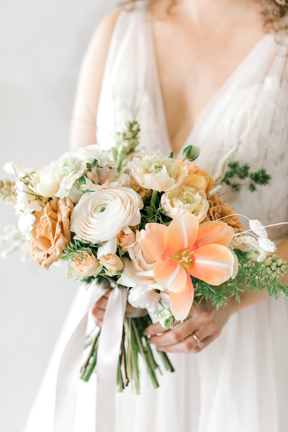The wedding bouquet with white, peachy and blush blooms plus greneery and ribbons