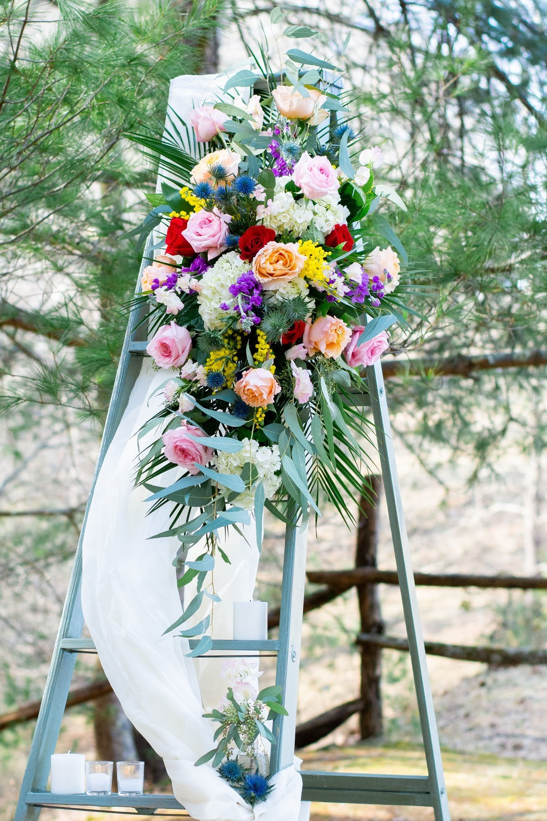 The wedding decor was done with a ladder, colorful blooms, candles and airy fabric