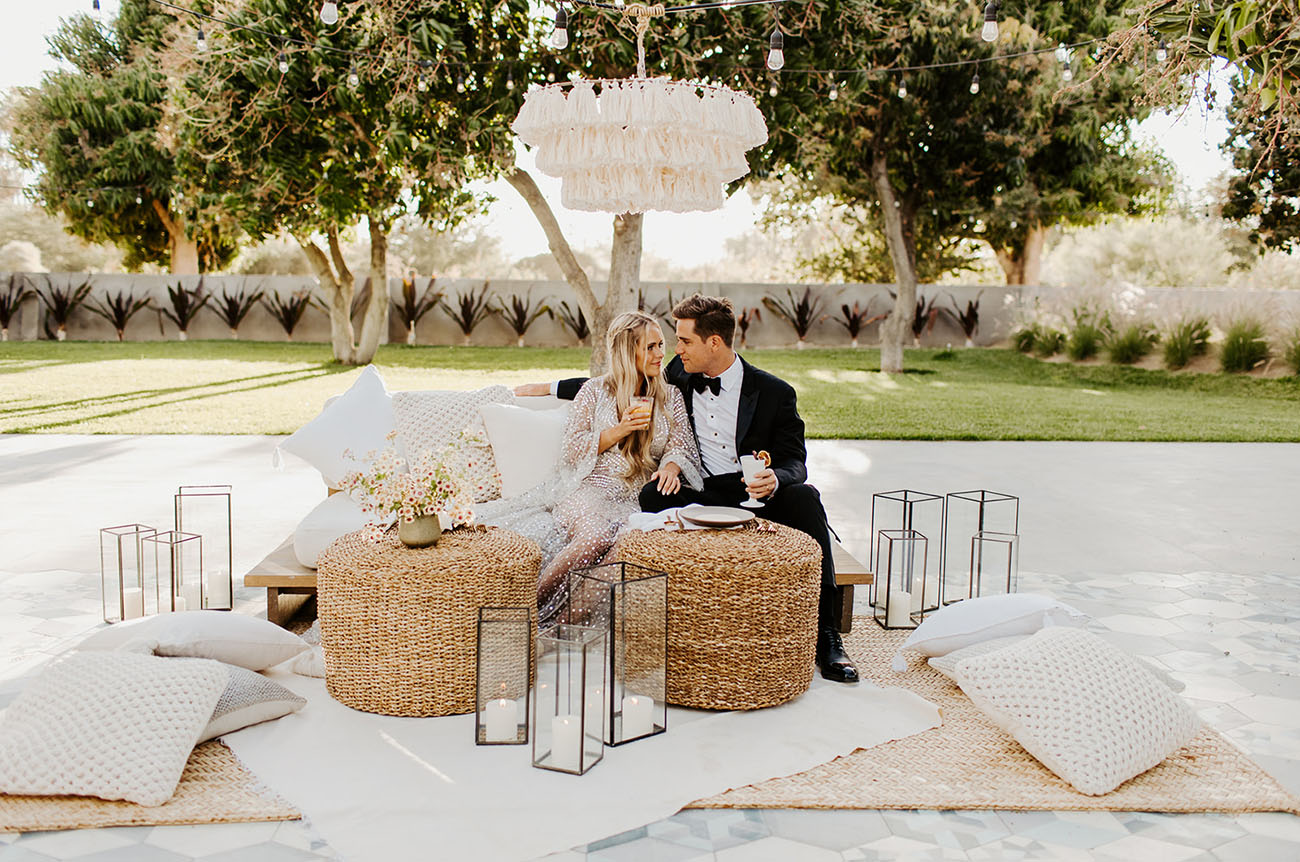 The wedding lounge was done boho, with a tassel chandelier, neutral pillows and jute ottomans