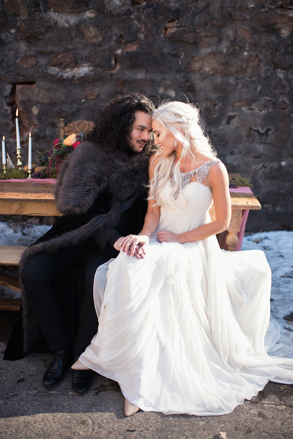 a Daenerys inspired bridal outfit with a draped wedding dress with an embellished neckline and a braided half updo