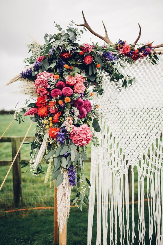 a colorful wedding backdrop done with macrame, antlers and super bright blooms on pink, red and purple for a woodland wedding