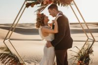 07 a hexagon arbor wedding arch decorated with herbs, greenery, bright blooms and grasses for a desert wedding