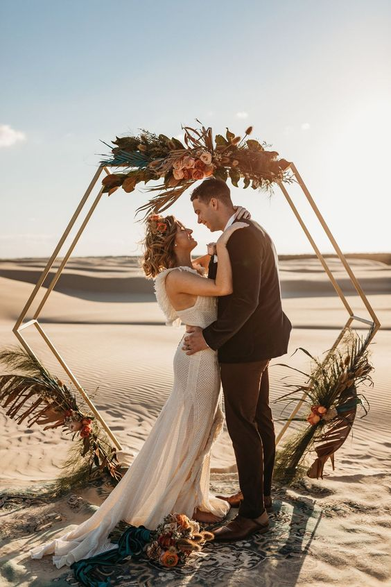 a hexagon arbor wedding arch decorated with herbs, greenery, bright blooms and grasses for a desert wedding