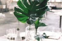 07 an arrangement of clear vases with a single tropical leaf in each for a minimalist tropical wedding