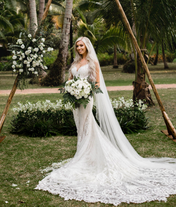 The bride was wearing a lace mermaid wedding dress with a train and a long veil