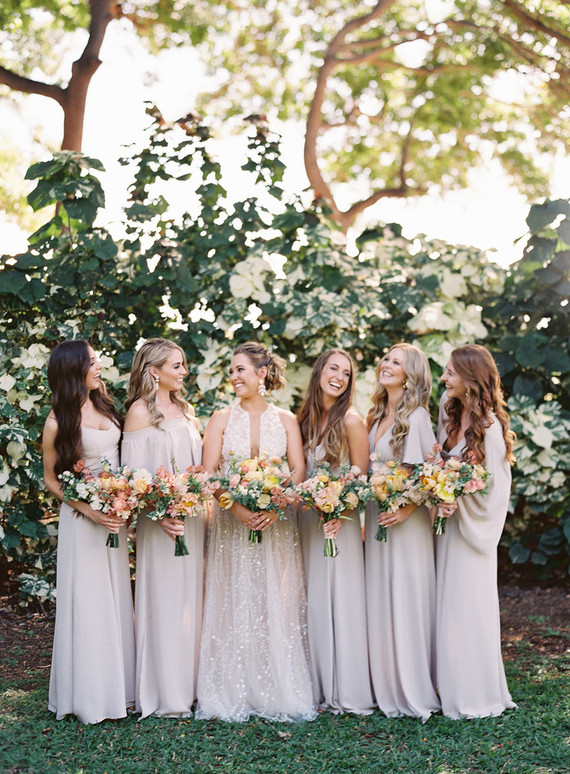 The bridesmaids were wearing mismatching off-white maxi dresses to make up a trendy white bridal party