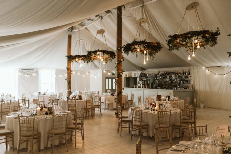 The wedding reception space was done with greenery chandeliers and bulbs and draperies