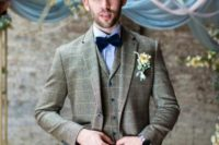 08 a brown windowpane print three-piece suit with blue buttons, a blue shirt, a navy velvet bow tie