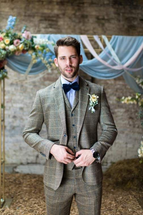 a brown windowpane print three piece suit with blue buttons, a blue shirt, a navy velvet bow tie