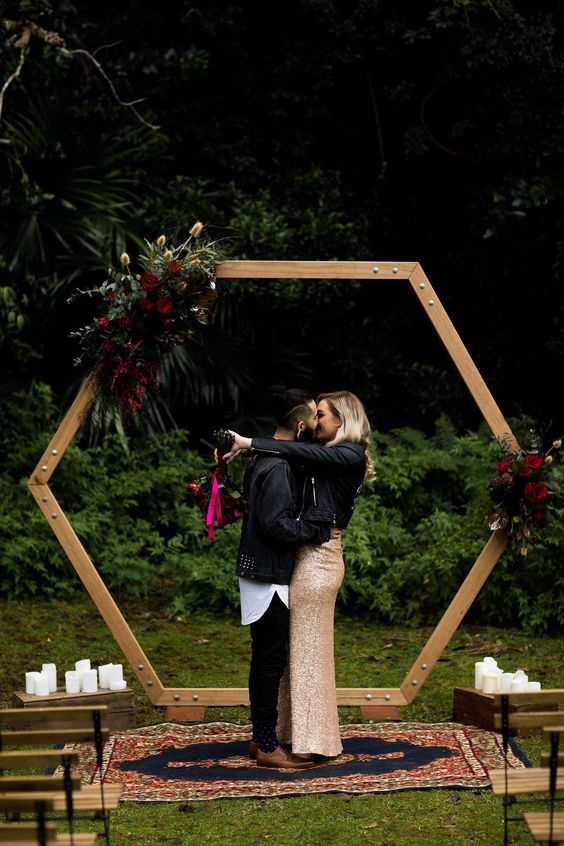 a hexagon arbor arch with greenery and burgundy and purple blooms plus candles around for a fall boho wedding