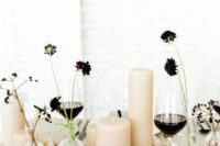 08 a wedding centerpiece of blush pillar candles and dark blooms in clear vases plus berries