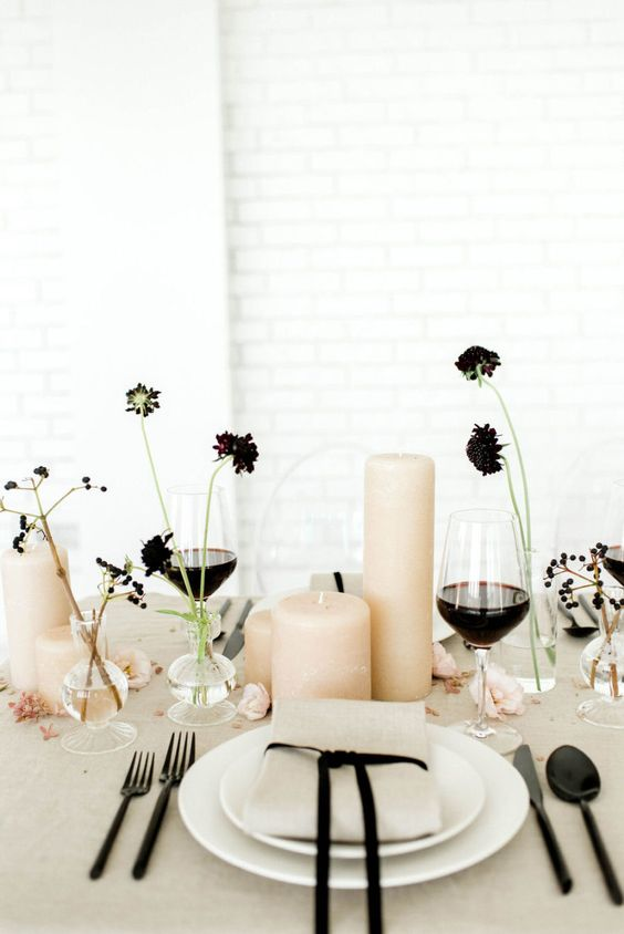 a wedding centerpiece of blush pillar candles and dark blooms in clear vases plus berries