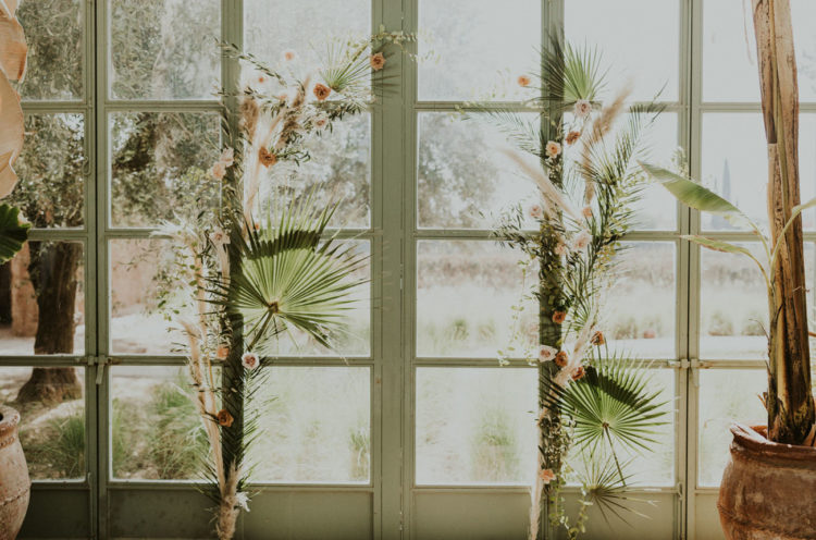 The wedding arch was done with palm fronds, blush blooms and pampas grass
