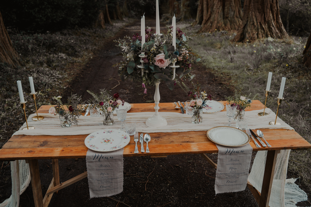 The wedding tablescape was done with an ethereal runner, floral plates, greneery and blooms, a candelabra decorated with florals