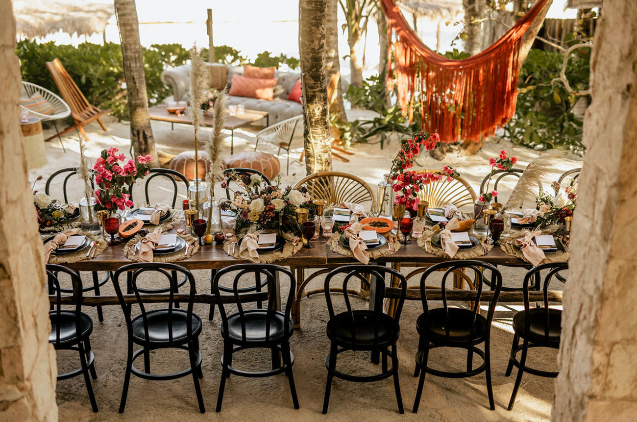 The wedding tablescape was done with bright florals, tropical fruits, fringe and colorful glasses
