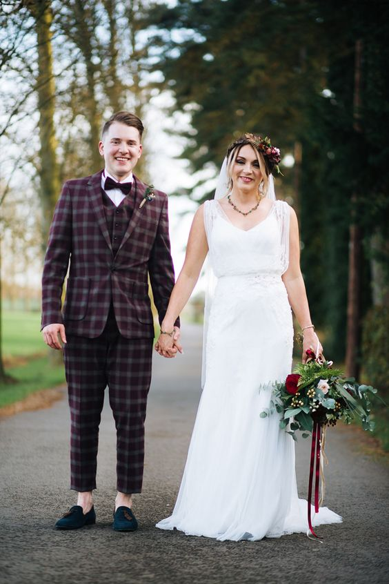 a burgundy checked three-piece wedding suit, a white shirt, a burgundy velvet bow tie and teal tassel loafers