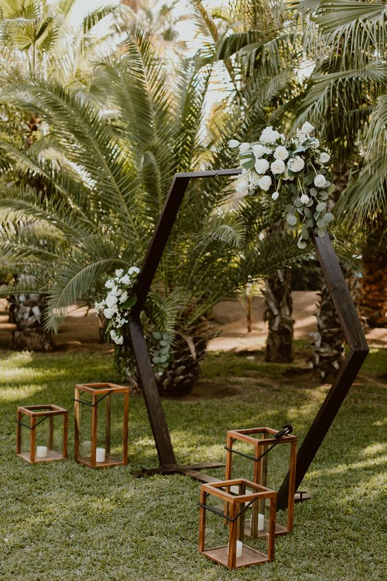 a dark stained hexagon wedding arch with lush greenery, white roses and tulips plus candle lanterns for a tropical wedding