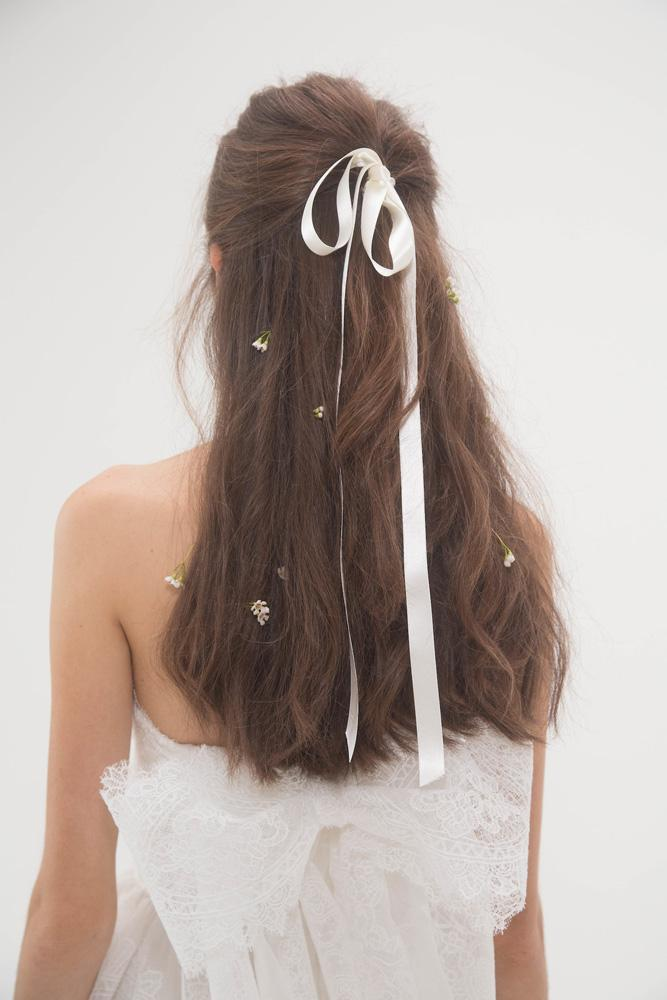 romantic half up wedding hairstyle with a white ribbon and fresh flowers for a beautiful and girlish feeling