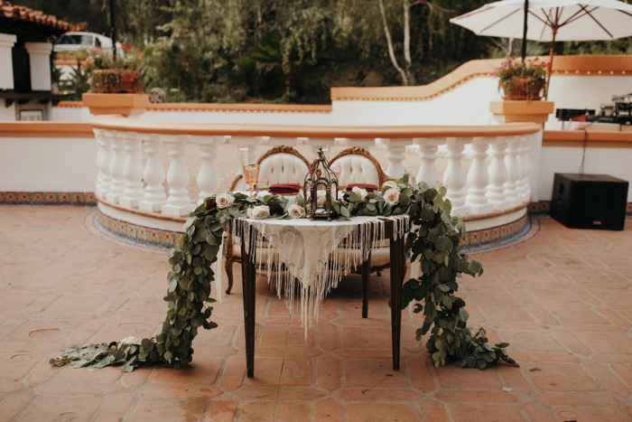 The sweetheart table was done with a macrame tablecloth with fringe, a lush greenery and blush bloom table runner and a candle lantern
