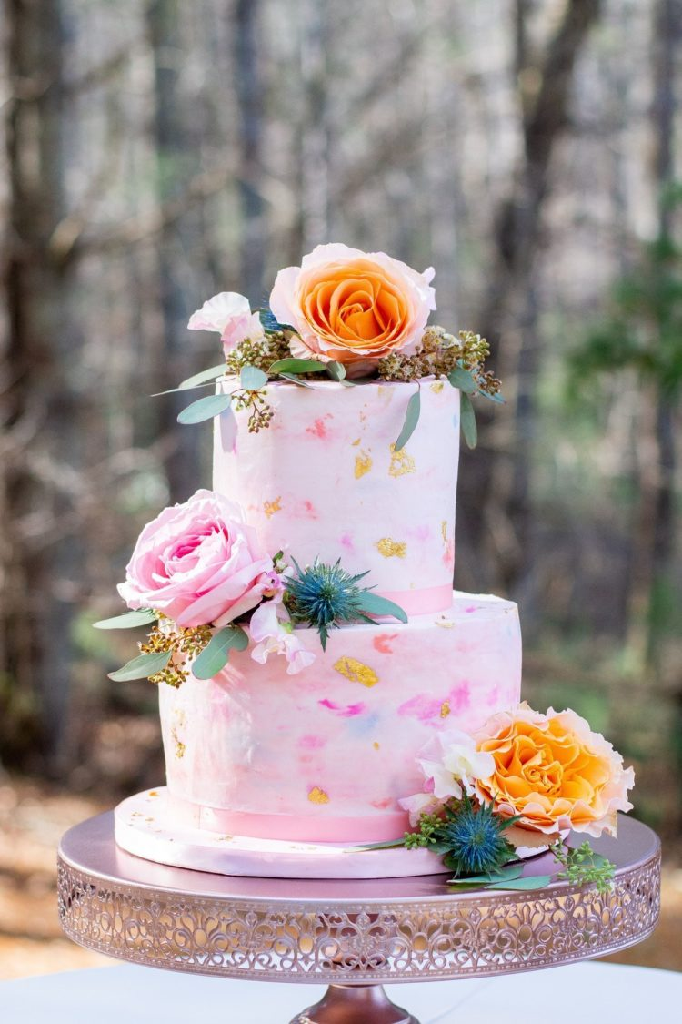 The wedding cake was a pink one, with watercolor brushstrokes in bold colors and gold leaf plus bright blooms and thistles