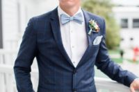 10 a chic navy windowpane print suit, a white shirt, a powder blue bow tie and a colorful floral boutonniere