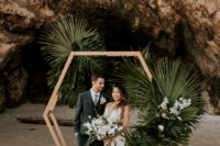 10 a hexagon wedding arch decorated with large tropical leaves and white orchids feels very boho and tropical-like