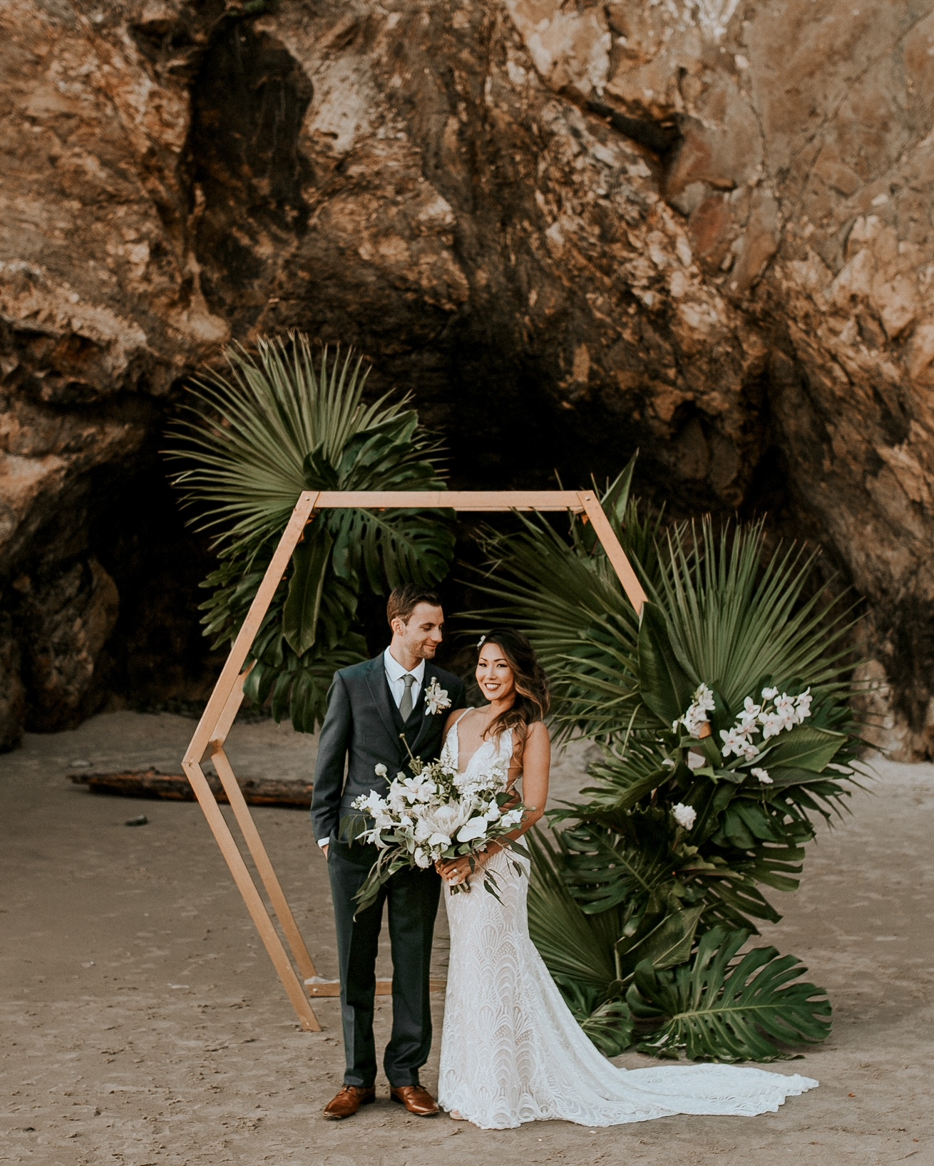 a hexagon wedding arch decorated with large tropical leaves and white orchids feels very boho and tropical like