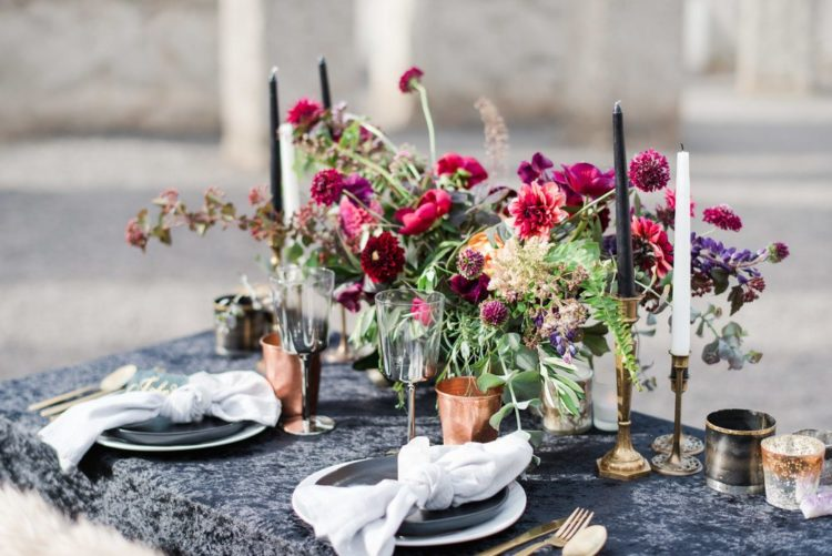 a lush and bold wedding table setting with a black tablecloth, a bright floral centerpiece and copper mugs