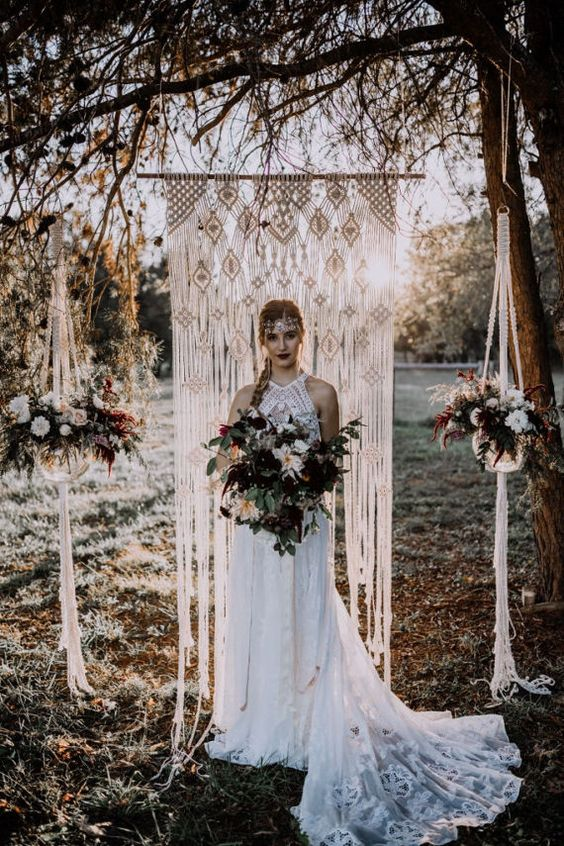 a macrame wedding backdrop with potted blooms hanging on each side of the backdrop