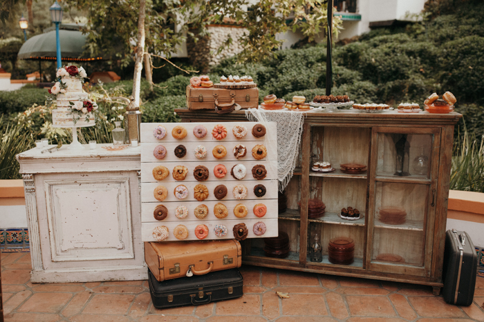 The dessert table was done with vintage suitcases and sideboards plus a trendy donut wall