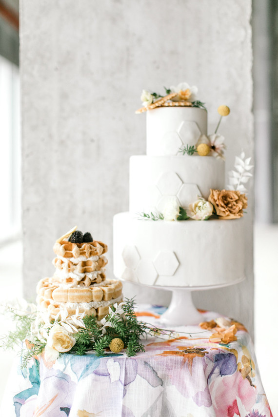 The wedding dessert table featured a waffle cake topped with berries and fruits, and a white honeycomb cake withh blooms and billy balls