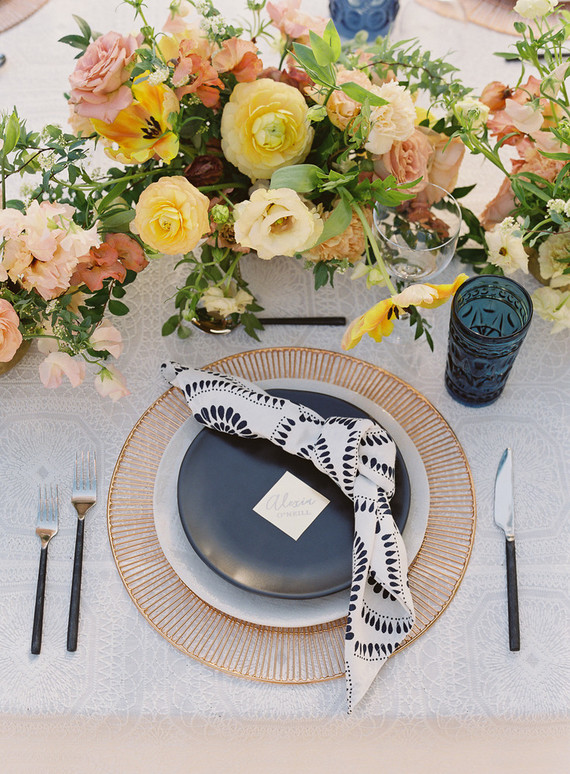 The wedding tablescape was done with lush florals, copper chargers, black and grey plates and navy glasses