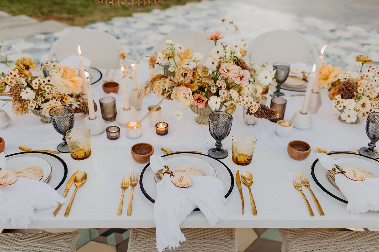 The wedding tablescape was done with lush neutral, rust and pink florals, gold cutlery, amber glasses and candles