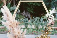 11 a hexagon wedding arch decorated with pampas grass and pink blooms on one side and ombre blooms on the other side, from whiet to rust