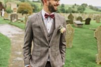 11 a stylish checked beige three-piece suit, a white shirt with copper buttons, a burgundy bow tie