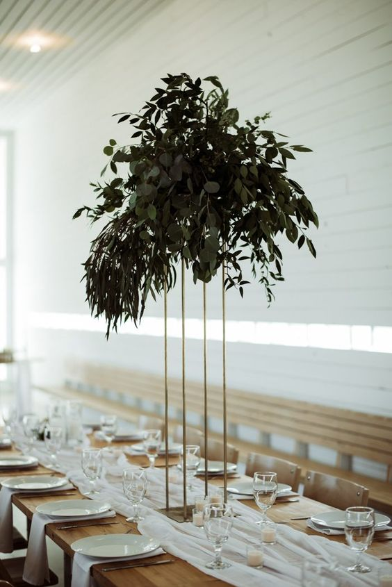 a tall minimalist wedding centerpiece on a gilded stand and with lush textural greenery won't take much table space