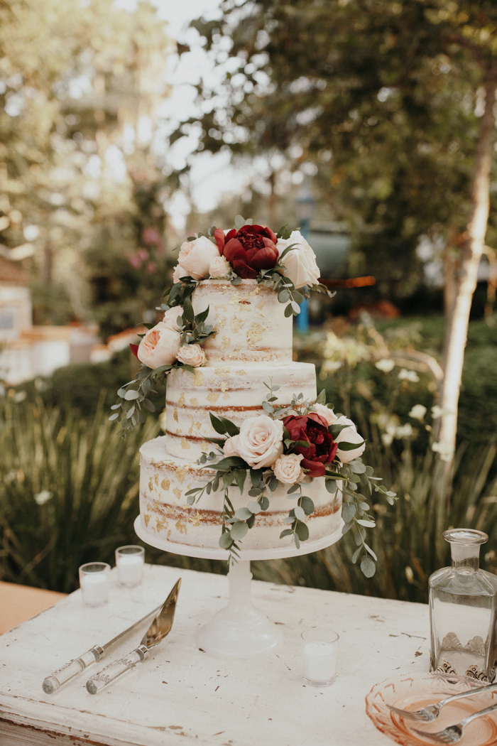 The naked wedding cake was decorated with gold leaf and blush and burgundy blooms plus eucalyptus