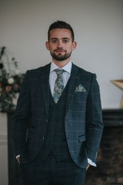 a graphite grey checked three-piece suit, a white shirt, a floral print tie and a matching handkerchief