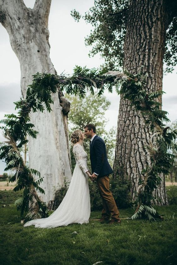 a hexagon wedding arch fully covered with greenery and ferns will be a perfect match for a woodland wedding